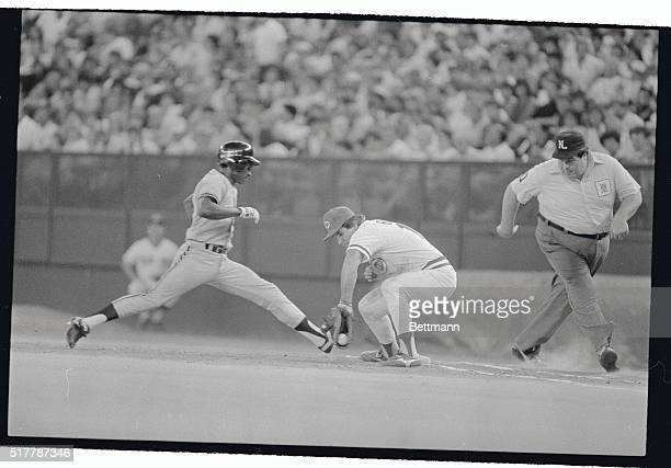 San Francisco's Jose Uribe gets back safely to first base as a pickoff throw starts to squirt out of the mitt of Reds player/manager Pete Rose in the...