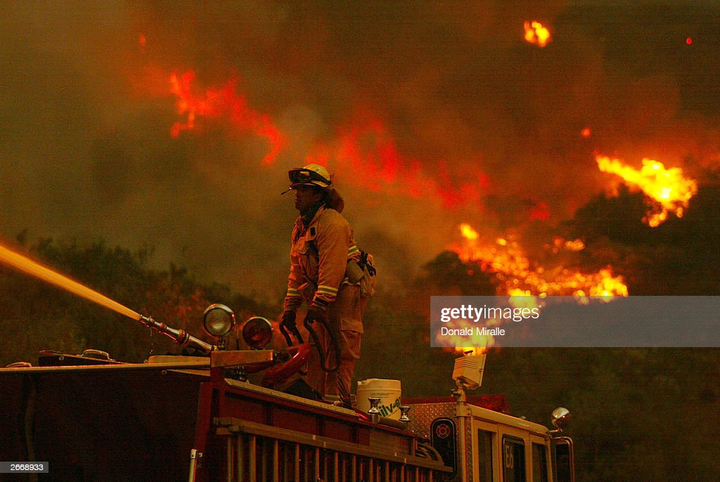 San Jose firefighter battles a portion of the Cedar Fire using a water spout from atop a firetruck October 27 2003 near Lakeside in San Diego...