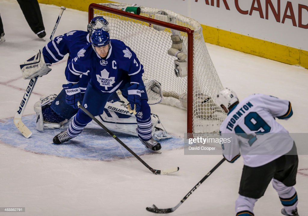 TORONTO ON DECEMBER 3 San Jose Sharks center Joe Thornton put the puck past Toronto Maple Leafs goalie James Reimer and Toronto defenseman Dion...