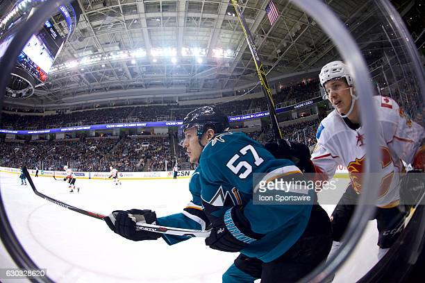 San Jose Sharks center Tommy Wingels holds off Calgary Flames defenseman Jyrki Jokipakka during the NHL game between the San Jose Sharks and the...