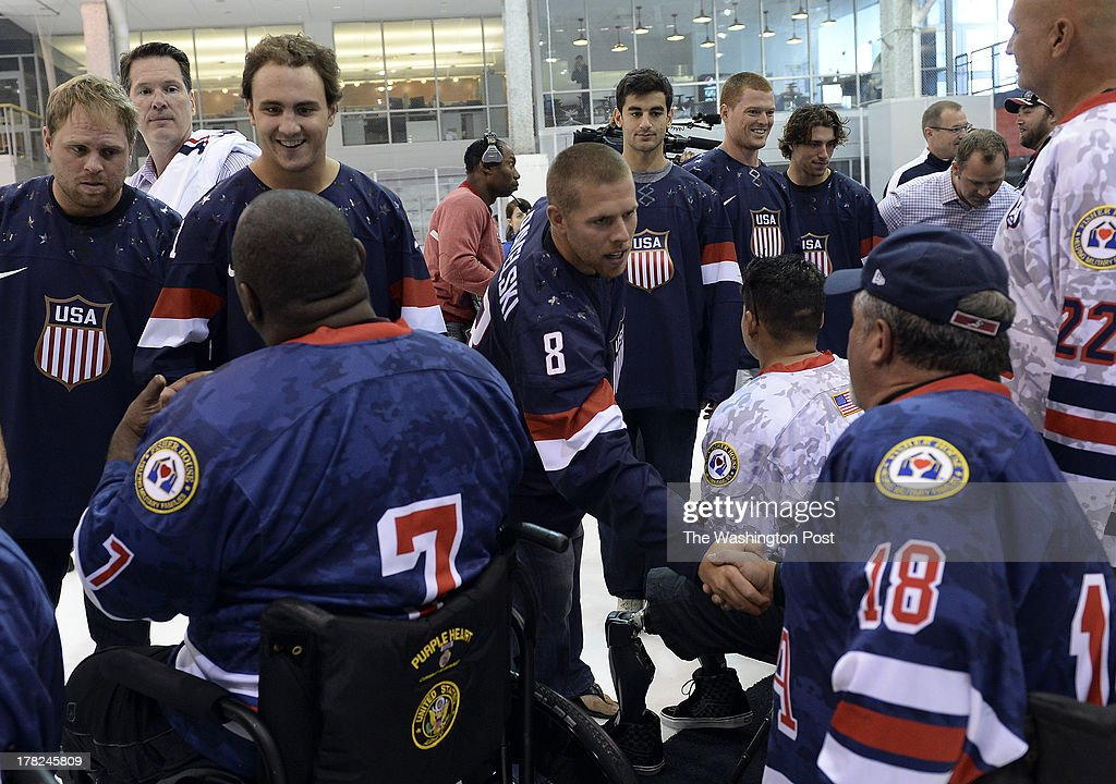 San Jose Sharks' forward Joe Pavelski leans in to shake the hand of a USA Warrior (Sled) Hockey player after the unveiling of the 2014 Winter Olympic team jersey during the National Team Orientation Camp at Kettler Capitals IcePlex on Monday, August 26, 2013.