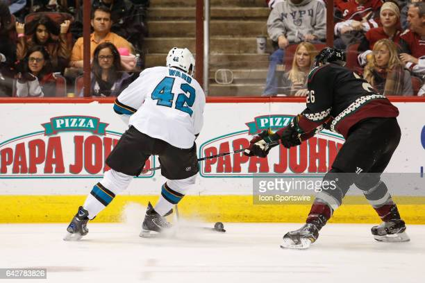 San Jose Sharks right wing Joel Ward tries to control the puck checked by Arizona Coyotes defenseman Michael Stone during the NHL hockey game between...