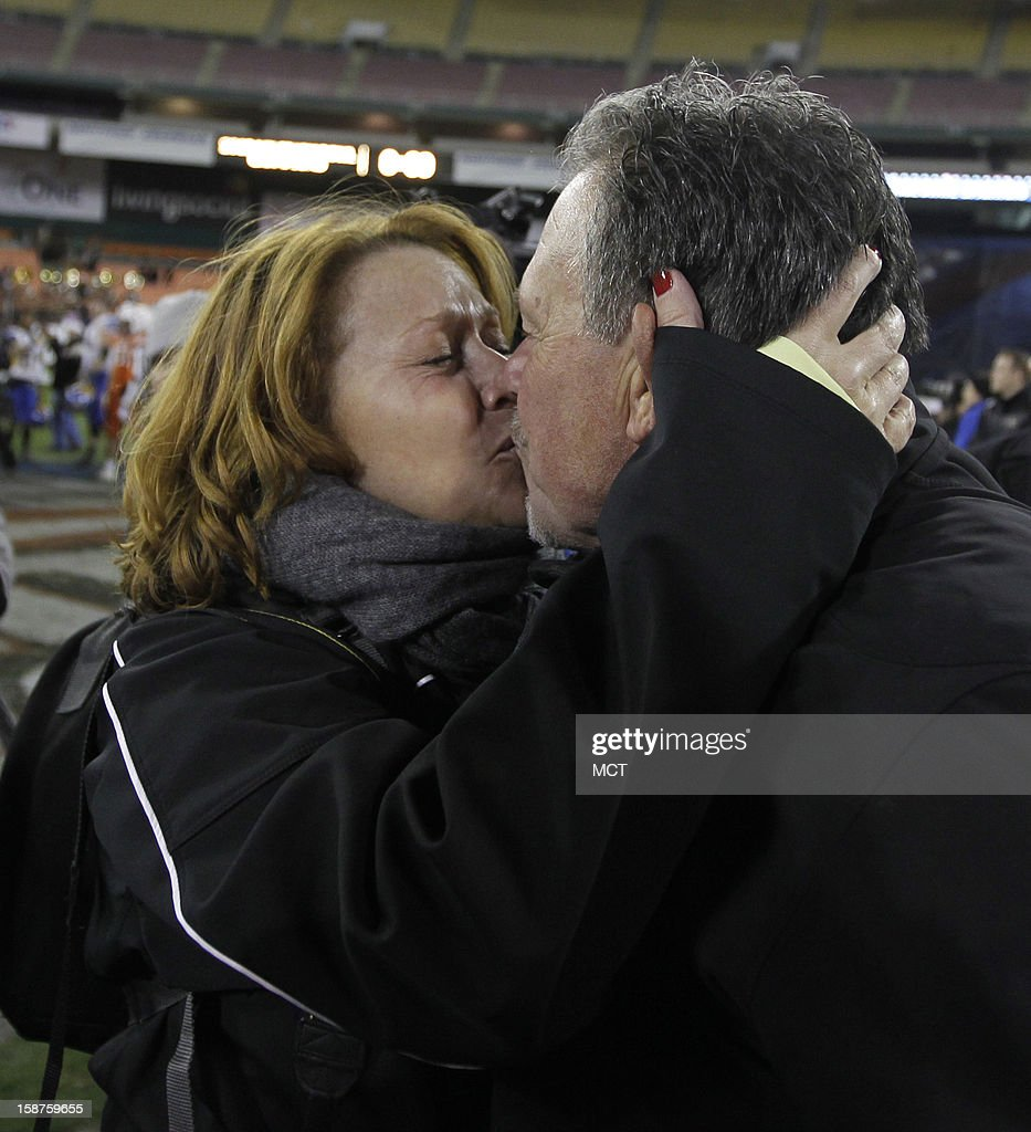 San Jose State interim head coach Kent Baer, right, kisses his girlfriend Erika Brunke, left, after the Spartans' game against Bowling Green at RFK Stadium in Washington, Thursday, December 27, 2012. San Jose State defeated Bowling Green 29-20.