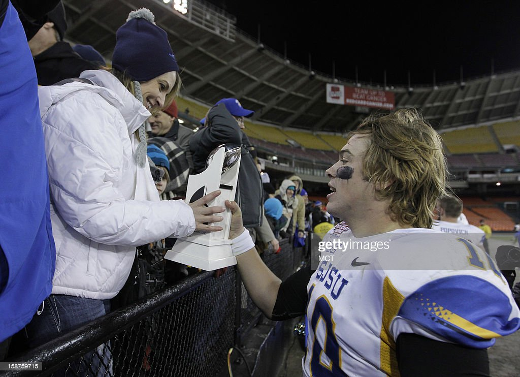 San Jose State quarterback David Fales, right, show his mother Tonia Fales, left, his Military Bowl MVP trophy after the Spartans' game against Bowling Green at RFK Stadium in Washington, Thursday, December 27, 2012. San Jose State defeated Bowling Green 29-20.