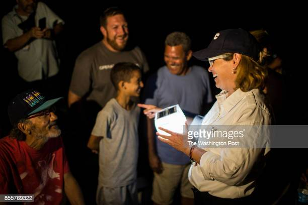 San Juan Mayor Carmen Yulin Cruz hands in solar lamps to La Perla Residents Hurricane Maria passed through Puerto Rico leaving behind a path of...