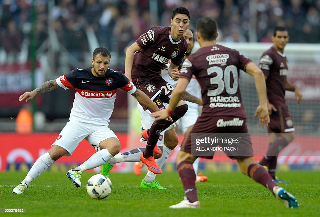 San Lorenzo's midfielder Franco Mussis (L) vies for the ball with Lanus' midfieldesr Miguel Almiron (C) and Ivan Marcone during an Argentina First Divison football final match at the Momnumental stadium in Buenos Aires, Argentina, on May 29, 2016. / AFP / ALEJANDRO