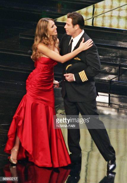 Soccer player Francesco Totti's wife Italian showgirl Ilary Blasi hugs US actor John Travolta on the stage of the Ariston Theatre during the 56th...