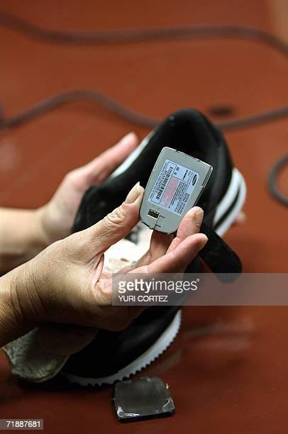 Un empleado de la Direccion de Centros Penales muestra 14 de septiembre de 2006 en San Salvador una bateria para telefono movil la cual le fue...