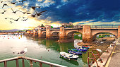 Idyllic and stunning coastal town in Spain. Bridge over the sea and sunset seascape. Boats in the harbor.
