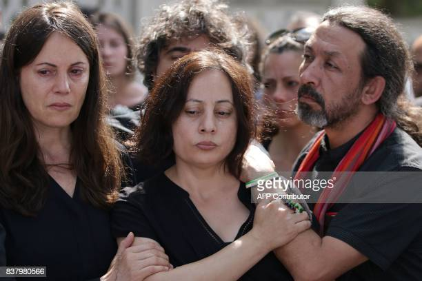 Sana and Najat sisters of late Syrian actress and activist Fadwa Suleimane mourn with Sana's husband Thaer during her funeral in Montreuil east of...