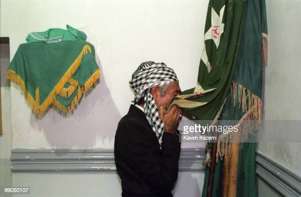 A dervish kisses the Kasnazani flags hanging on the corner of a Tekieh in Sanandaj Iran on the Unity Week called by Islamic Republic celebrating...