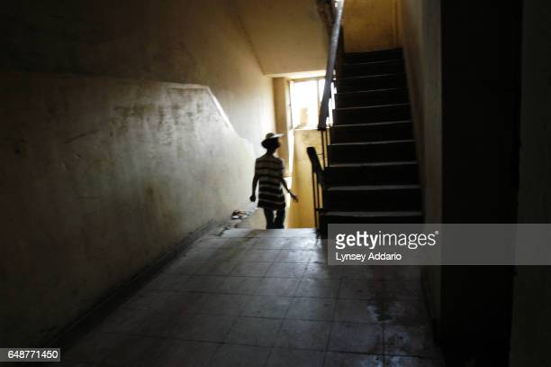 Sanaria during a visit to her mother after being placed in an orphanage walks down the stairs in the building where her family is now living while on...