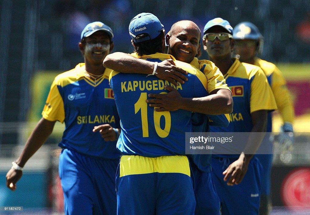 Sanath Jayasuriya of Sri Lanka celebrates with team mate Chamara Kapugedera after taking the wicket of Daniel Vettori of New Zealand during the ICC...