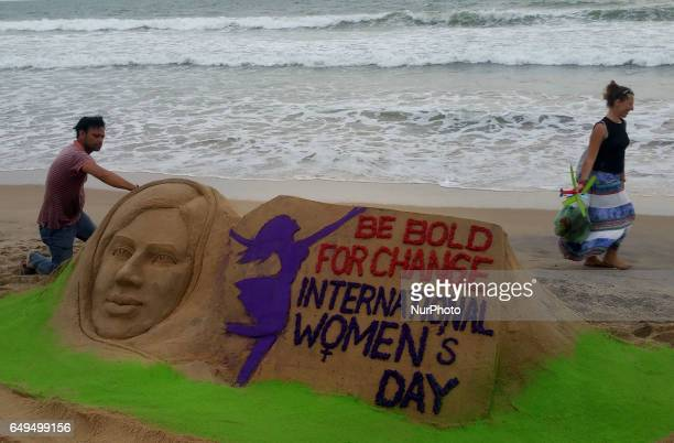 A sand art for purpose of International Womens Day is seen on the Bay of Bengal Seas eastern coast beach at Puri 65 km away from the eastern Indian...