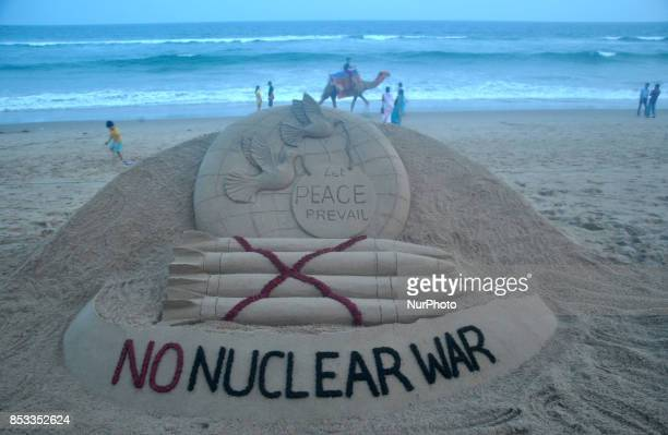 A sand art is seen at the Bay of Bengal Sea's eastern coast beach on 25 September 2017 creating by sand artist Sudarshan Pattnaik to spread message...