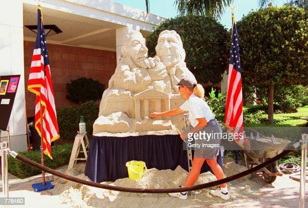 Sand artist Cathy Colvin chisels away at this 5 foot sculpture depicting Vice President Al Gore arm wrestling George Bush Jr atop the White House on...