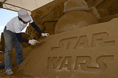 Sand artist Kasuhiko Chaen works on the sand sculpture ahead of the promotional exhibition for 'Star Wars The Force Awakens' on October 6 2015 in...