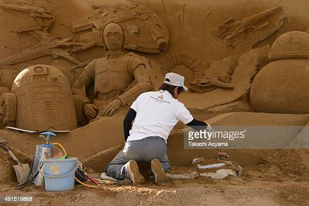 Sand artist Katsuhiko Chaen works on the sand sculpture ahead of the promotional exhibition for 'Star Wars The Force Awakens' on October 6 2015 in...