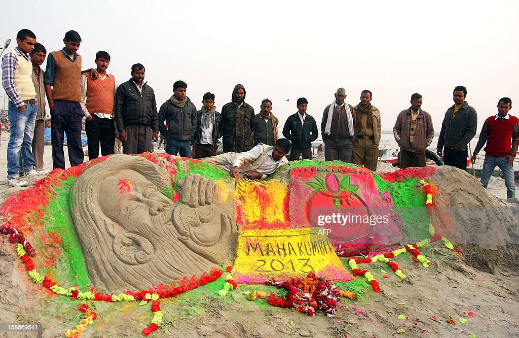 Sand artist Raj Kapoor creates a sand sculpture at the Sangam for welcoming tourists from all over the world through his sculpture in the upcoming Kumbh mela festival in Allahabad on December 23, 2012. The Kumbh Mela, which is scheduled to take place in the northern Indian city in January and February 2013, is the world's largest gathering of people for a religious purpose and millions of people gather for this auspicious occasion. AFP PHOTO/ Sanjay KANOJIA