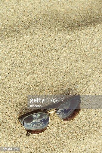 Sfondo sabbia con occhiali da sole sulla spiaggia : Foto stock