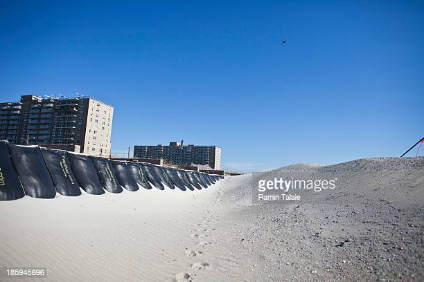 Sand bags and constructed sand dunes protect the foundations to the historic Rockaway boardwalk after it was washed away during Hurricane Sandy on...