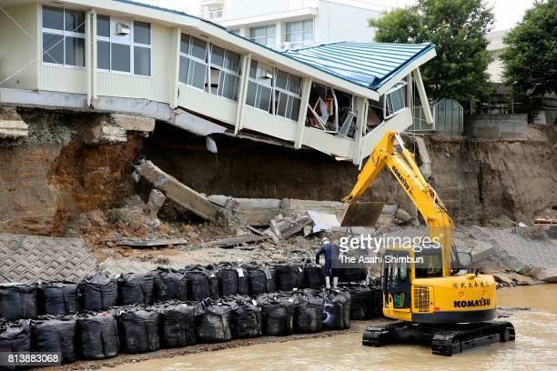 Sand bags are unloaded at the bank of Katsuragawa River next to the Hiramatsu Junior High School on July 13 2017 in Asakura Fukuoka Japan Death toll...