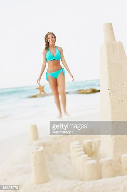 Sand castle and woman holding sea star