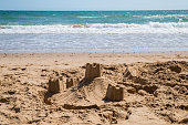 Sandcastles on a sandy beach with the sea in the background.