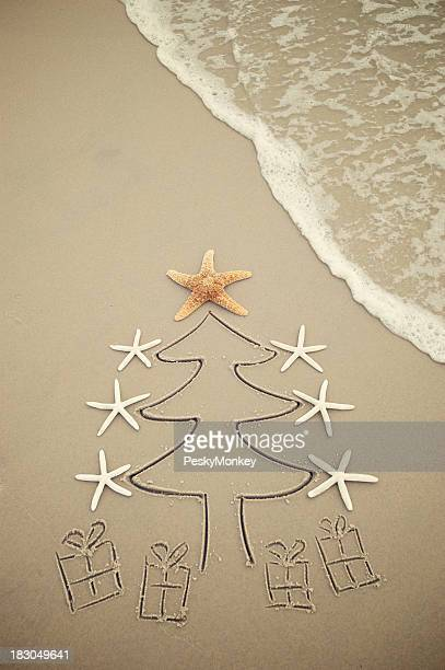Sable Sapin de Noël avec des cadeaux sur la plage
