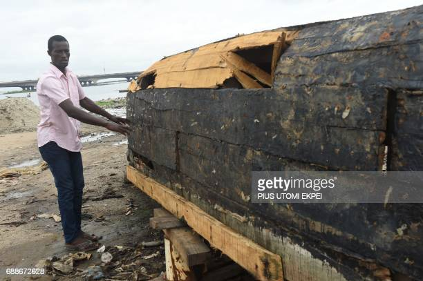 Sand dealer Ade Omowumi points to boat vandalised by policemen who came to enforce eviction notice served on residents of IlajeBariga waterfront slum...