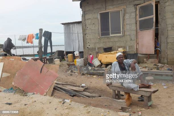 A sand dealer sits in front of a house despite an eviction notice served on residents of IlajeBariga waterfront slum mostly fishermen and sand...