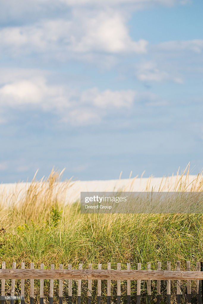 A sand dune, fence and blue sky. : Foto de stock
