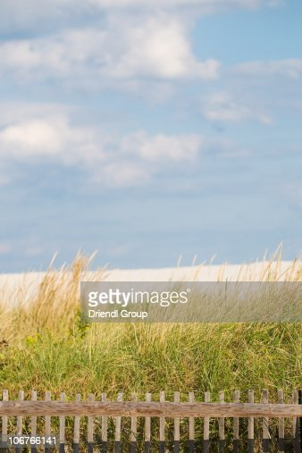 A sand dune, fence and blue sky. : Stock Photo