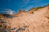 sand dune in sandbanks provincial park with wispy clouds
