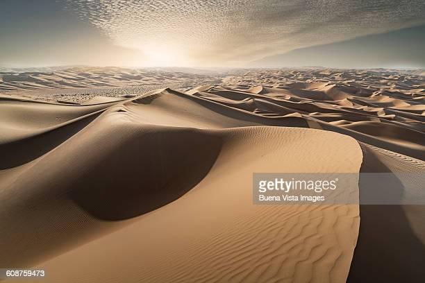 Sand dunes in a desert at sunset