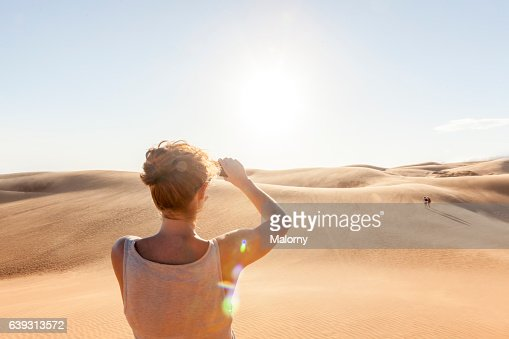 Sand dunes, woman taking pictures with her smartphone