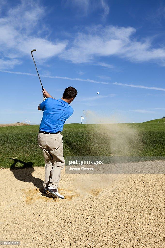 Sand flies after a man makes a clean golf shot.