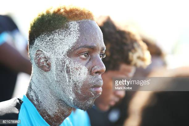 Sand is seen on the face of Oakland Duncan of the Bahamas as he watches on during the boy's beach soccer bronze medal final match between Antigua the...
