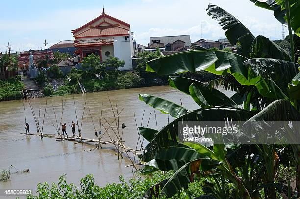 Sand miners make a bamboo bridge to facilitate diving for sand in the middle of the Brantas River The miners dive into the river to dredge sand and...