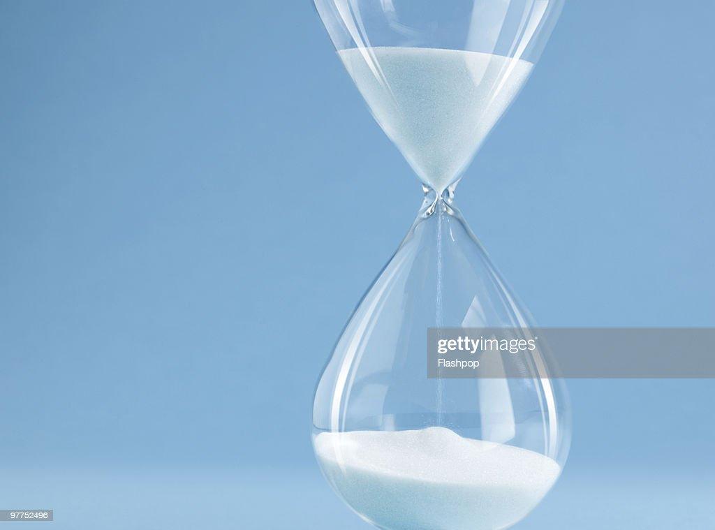 Sand pouring through egg timer : Stock Photo