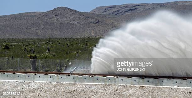 Sand rises from the track as a test sled is slowed during the first test of the propulsion system at the Hyperloop One Test and Safety site on May 11...
