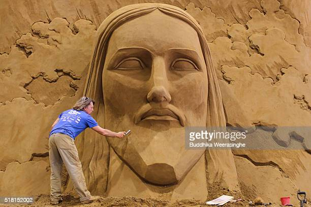 Sand sculptor Dan Belcher of the USA works on sand sculpture named Christ the Redeemer statue in Corcovado ahead of the eight annual exhibition...
