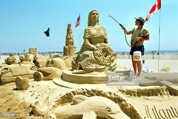 Sand sculptor Darlene Duggan waters down a sculpture made by a group of master sculptors June 20 2001 in Hampton Beach NH Competitors invited from...