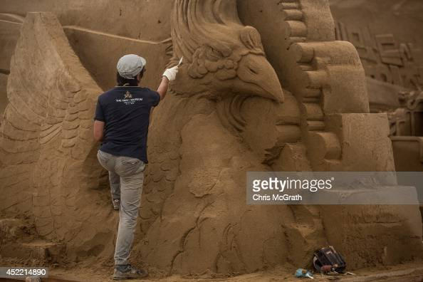 Sand sculptor Katsuhiko Chaen works on a large sand sculpture at the site of Yokohama Sand Art Exhibition Culture City of East Asia 2014 on July 16...