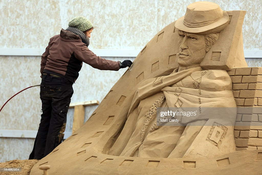A sand sculptor works on a <a gi-track='captionPersonalityLinkClicked' href=/galleries/search?phrase=Clint+Eastwood&family=editorial&specificpeople=201795 ng-click='$event.stopPropagation()'>Clint Eastwood</a> sand sculpture as pieces are prepared as part of this year's Hollywood themed annual Weston-super-Mare Sand Sculpture festival on March 26, 2013 in Weston-Super-Mare, England. Due to open on Good Friday, currently twenty award winning sand sculptors from across the globe are working to create sand sculptures including Harry Potter, Marilyn Monroe and characters from the Star Wars films as part of the town's very own movie themed festival on the beach.