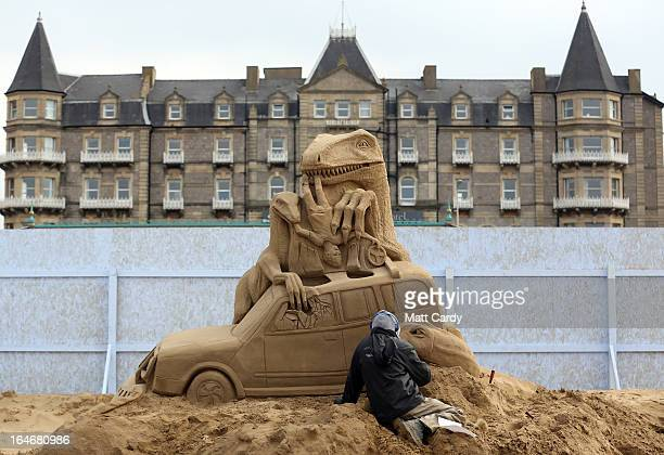 A sand sculptor works on a Jurassic Park themed sand sculpture as pieces are prepared as part of this year's Hollywood themed annual WestonsuperMare...