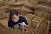 Sand sculptor Zhang Yan of China works on the Chinese section of a large sand sculpture at the site of Yokohama Sand Art Exhibition Culture City of...