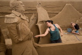 Sand sculptors Sue McGrew of the USA and Leonardo Ugolini of Italy work on the American/ Japan section of a large sand sculpture at the site of...