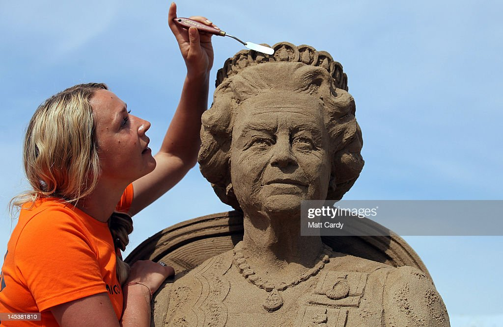 Sand sculpture artist Nicola Wood completes a sand sculpture she has created of Queen Elizabeth II at the annual Weston-super-Mare Sand Sculpture festival on May 28, 2012 in Weston-Super-Mare, England. Now in its seventh year, the festival, which opens to the public on Friday, features sand sculptures from award-winning artists from across the globe. Using 4000 tonnes of Weston beach sand this year's giant sand art display, created by 15 international artists on the theme Fun and Games, runs throughout the summer until September 9.