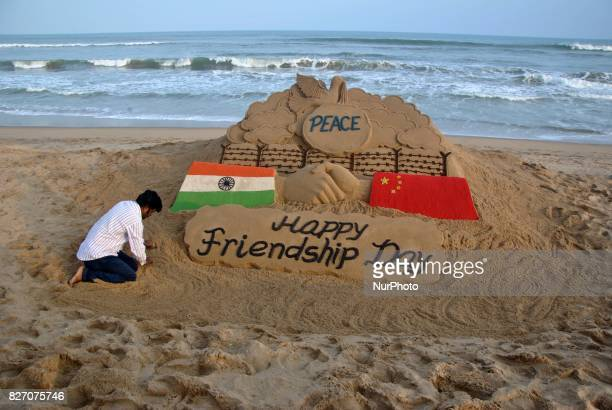 A sand sculpture creating by sand artist Sudarshan Pattnaik to spread message about ChinaIndia friendship on the International Friendship Day at the...